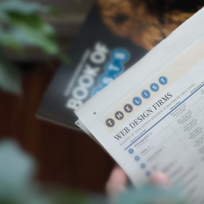 """a hand holding a newspaper listing top """"Web Design Firms"""" in front of a BBJ Book of Lists"""