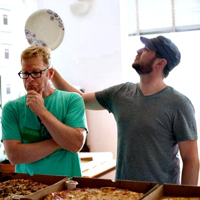 man longingly looks at pizza with another man holding a plate above his head