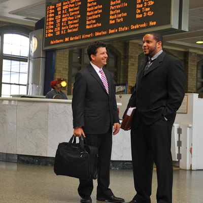 businessmen talking in train station